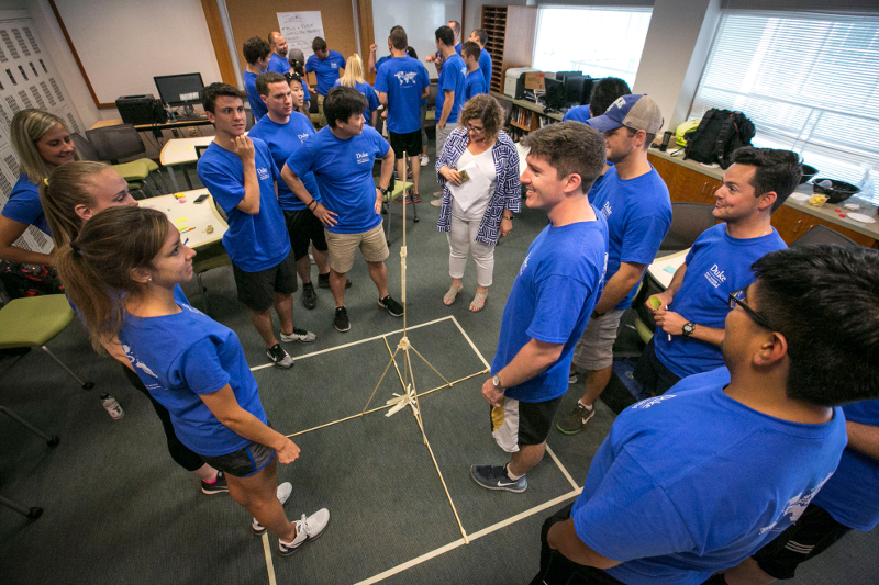 A group of students in blue shirts work on a project involving sticks in a tower shape