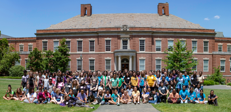 A large group of women pose in front of Duke Engineering's Hudson Hall