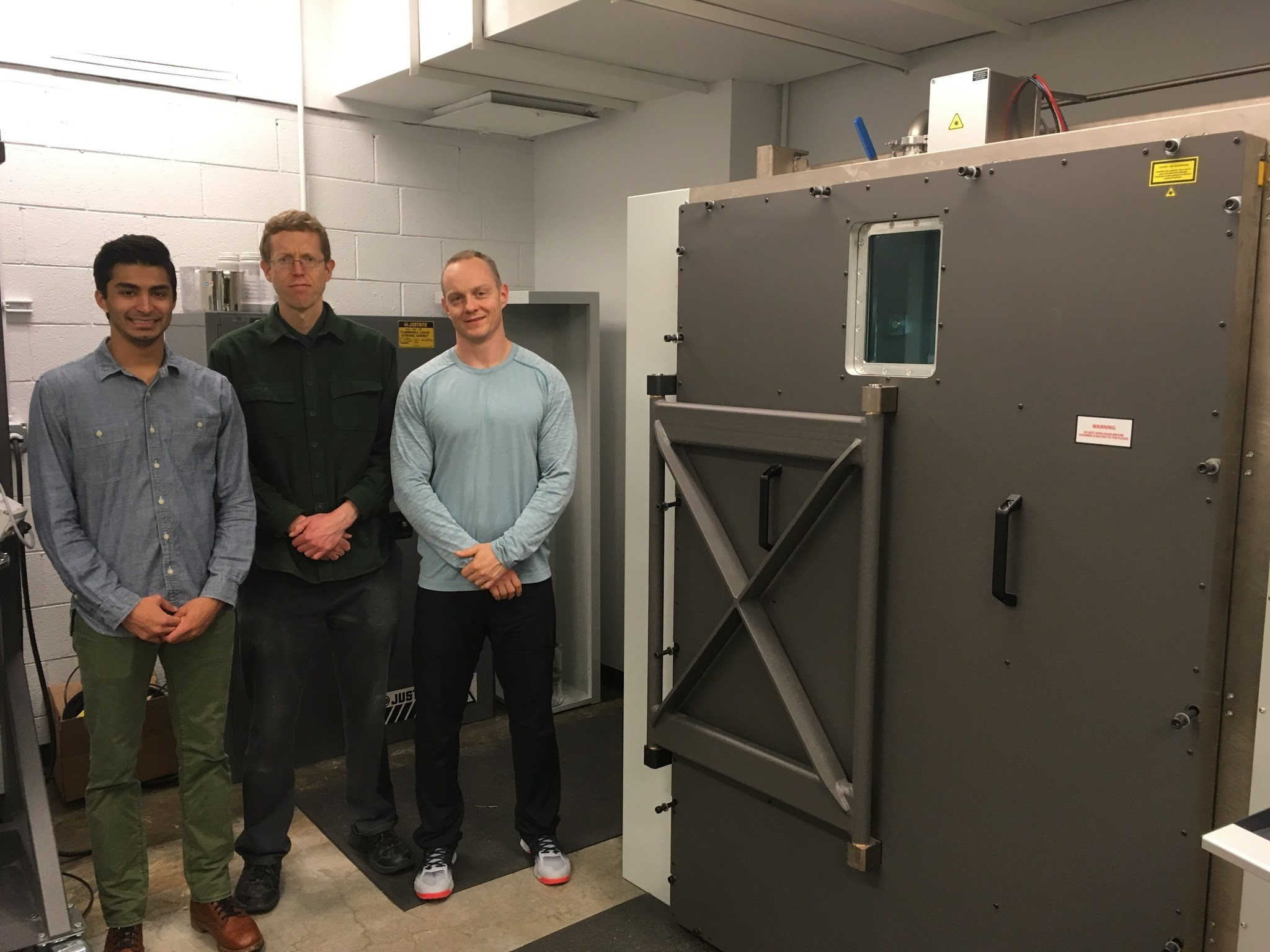 Kyle Dhindsa (Mechanical Engineering '17), Patrick McGuire (Senior Lab Administrator), and Professor Ken Gall stand beside the ProX DMP 320 Printer.