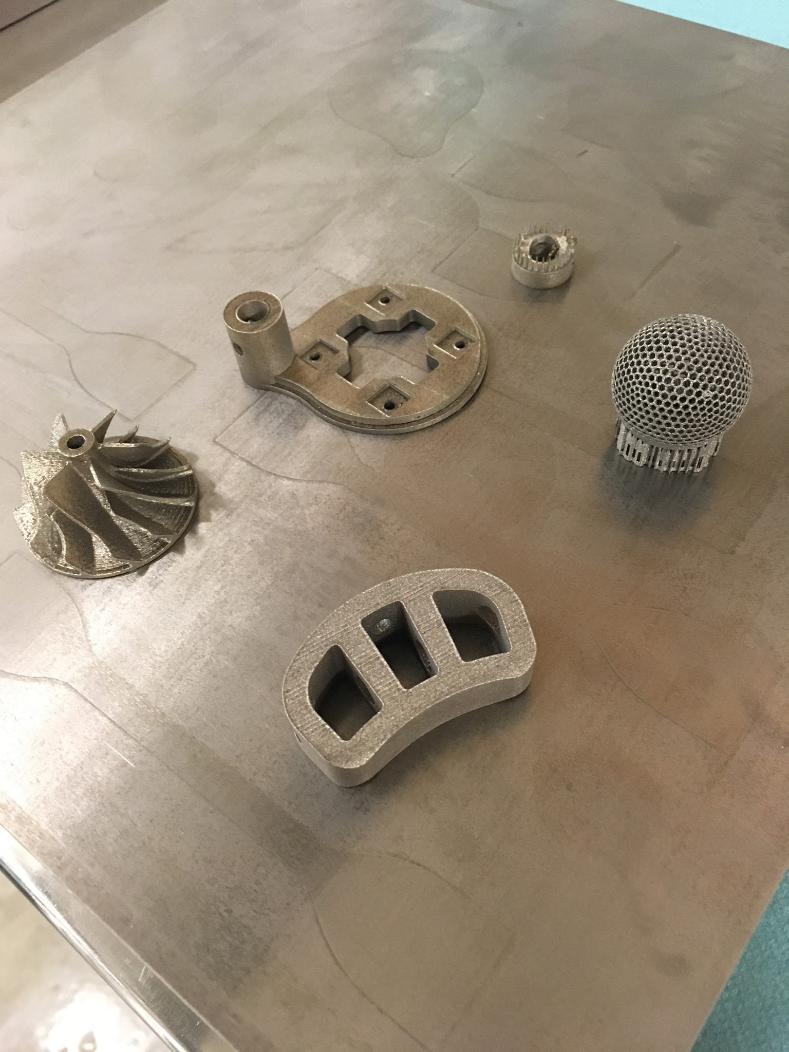 Printed parts on a titanium printing platform. From left to right, impeller, spinal fusion cage, brain electrode holder, ultrasound transducer electrode and metallic sphere with hexagonal mesh.
