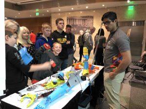 Kids around a table full of plastic prosthetics