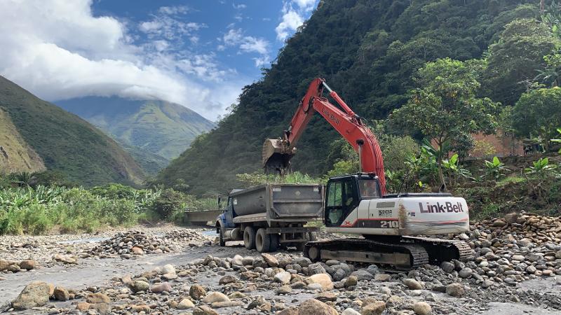 A large construction machine in a field in a jungle