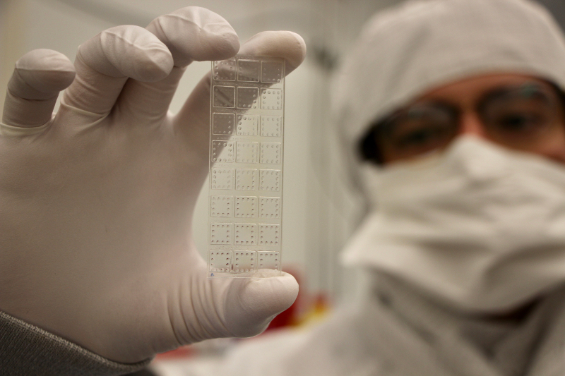A scientist in a clean room coat holds a small rectangular plastic slide with lots of squares