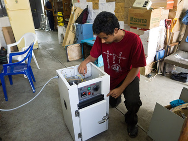 Engineering World Health student repairing a hot air sterilizer