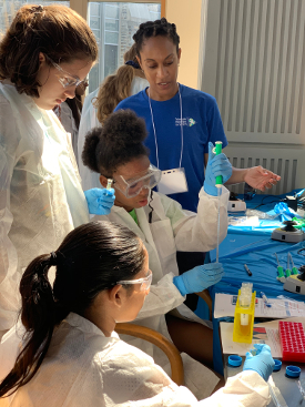 An older volunteer helps three girls with an experiment involving vials and safety equipment