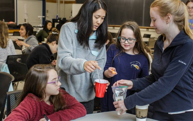 Two female Duke students work with middle school girls on a science experiment