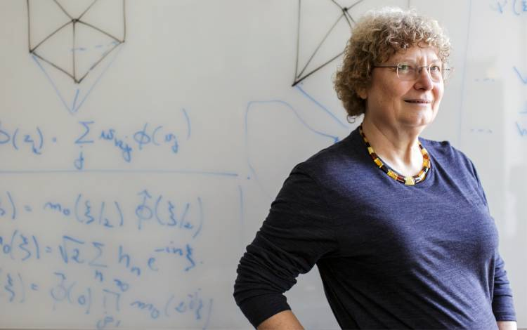 Ingrid Daubechies in front of a white board filled with mathematics