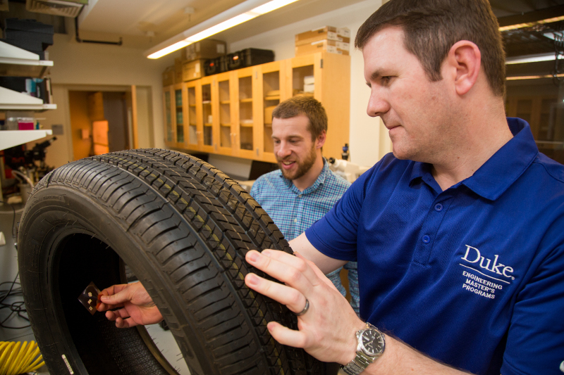 Professor Aaron Franklin and Joseph Andrews, a PhD student who led the original research on the tread wear sensor, demonstrate where the new sensor would be embedded in a commercial tire.