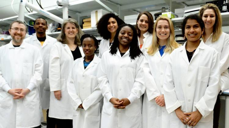 A group of researchers with white lab coats on standing in a laboratory