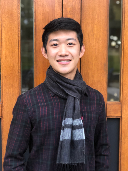 A young man in a scarf and plaid shirt