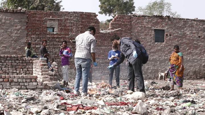 Students take samples of the air quality near a common roadside pile of burning trash