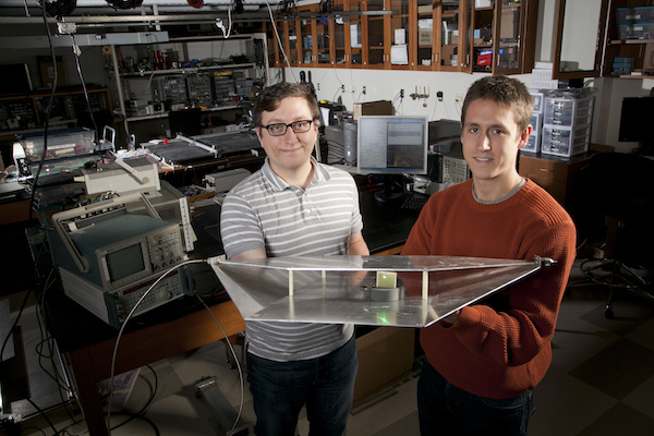 Duke engineering students Alexander Katko (left) and Allen Hawkes show a waveguide containing a single power-harvesting metamaterial cell, which provides enough energy to power the attached green LED.