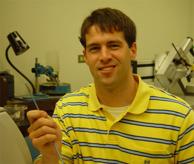 Herickhoff holds a catheter used to treat brain tumors