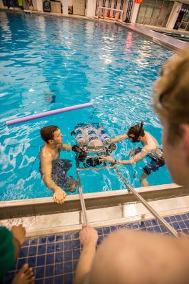 Logan Rooper E'17 and Austin McKee E'17 load Leviathan into the pool at Taishoff Aquatics Pavillion