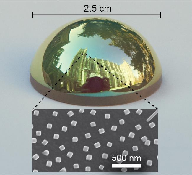 A curved object covered with the coating that absorbs all red light, which leaves the object with a green tint. A closer look reveals that the surface is covered with tiny 100 nanometer silver cubes.