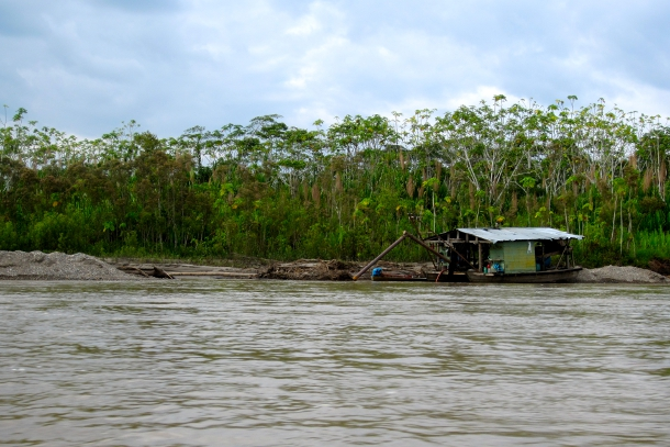 A small-scale gold mining operation docks along the Madre de Dios River in Peru. Small boats remove sediment from nearby riverbank where mercury is added to extract gold. Recently, the Peruvian Navy has begun to crackdown on mining operations directly on the river by bombing small boats such as this one.