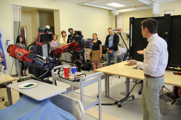 Assistant professor of nursing Ryan Shaw (Right) explains the robotic nursing platform to visitors during Monday's robotics student symposium.