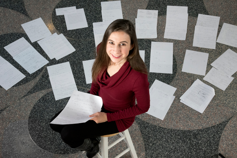 Cynthia Rudin sits before papers spread out on the floor to help her organize algorithms