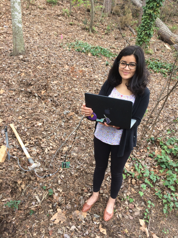 Pratiksha Sharma tests prototype devices designed to detect earthquakes with her computer in the woods