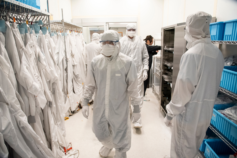 A line of people donning clean suits in a clean room lab