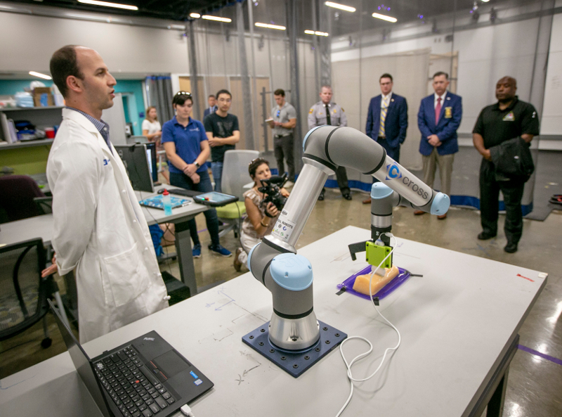 A man in a white lab coat standing by a robotic arm in front of a group of people