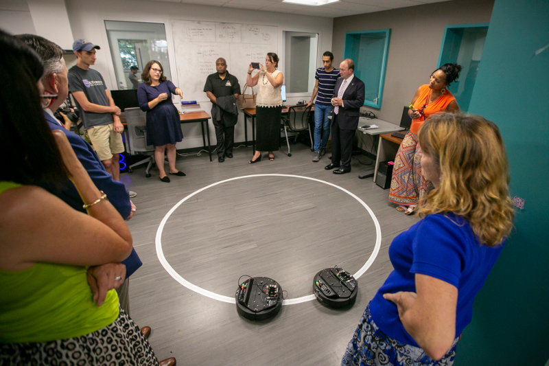A group of people stand around two small disc-shaped robots on the floor
