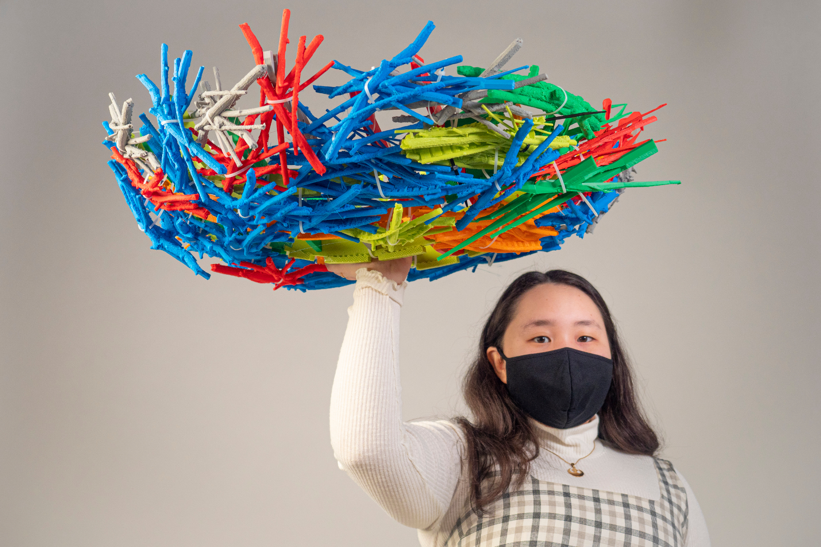 A young woman holding a large, multi-colored, plastic nest