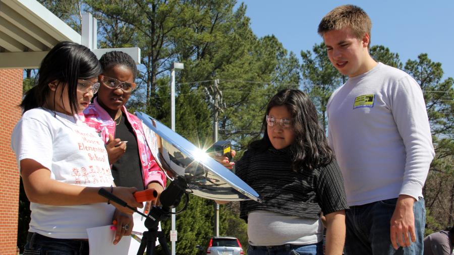 A Duke Engineering student teaches 5th grade students about solar energy with a hands-on activity