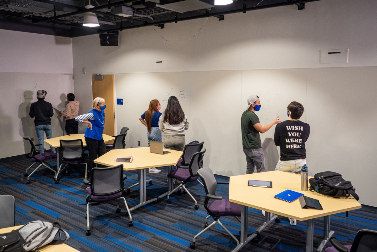 students write equations on whiteboard walls in an active learning classroom