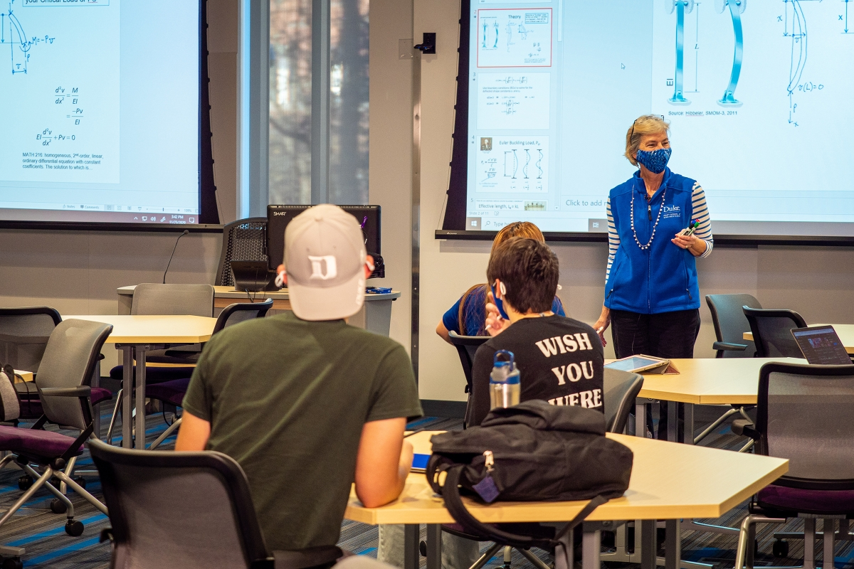 faculty member stands at a large screen teaching a class in an active learning classroom