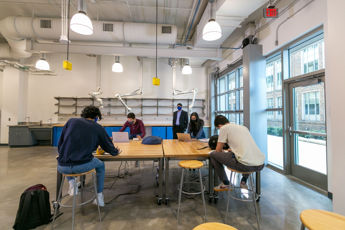 students work at laptops on tables in the Christensen Family Center for Innovation with Dean Bellamkonda in the background