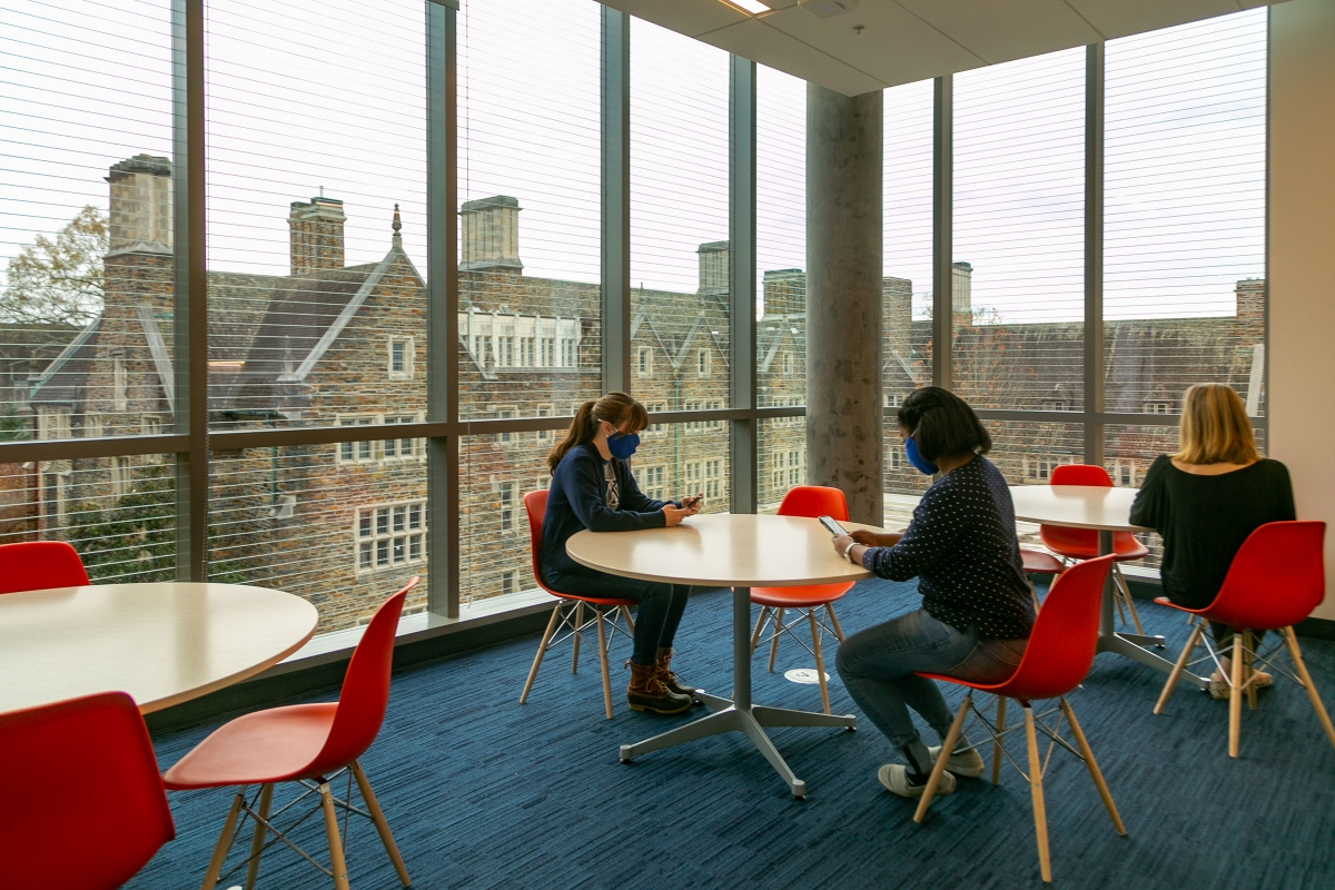 students check their phones at tables in a graduate student lounge with a view of West Campus through the windows