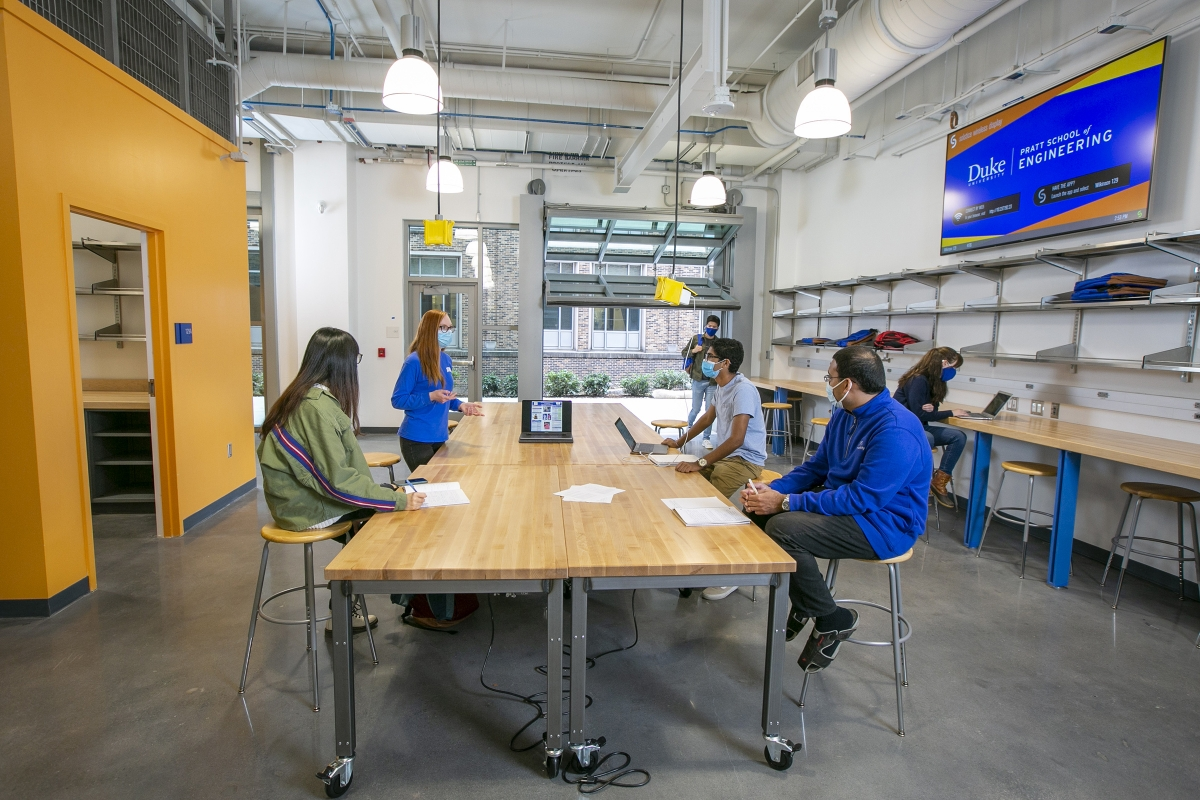 students work at a table in a garage lab while one student walks through the open garage door
