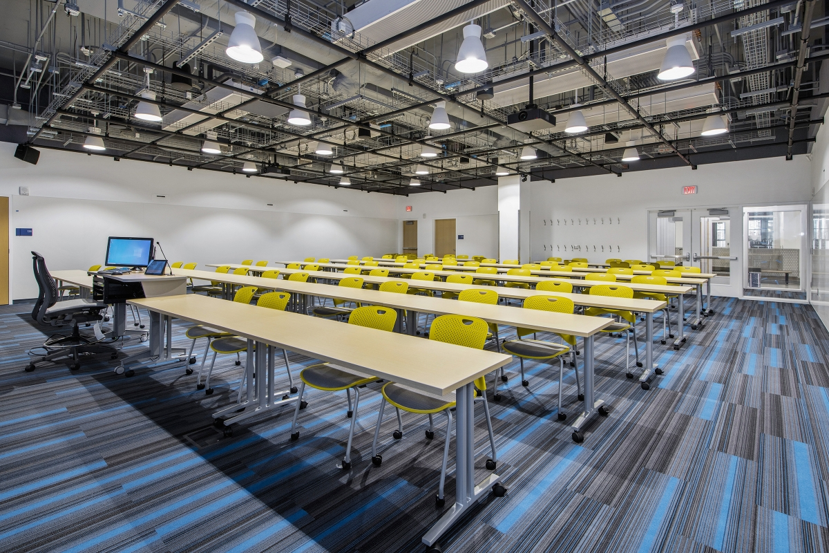 row of reconfigurable tables and bright yellow chairs in an active learning classroom
