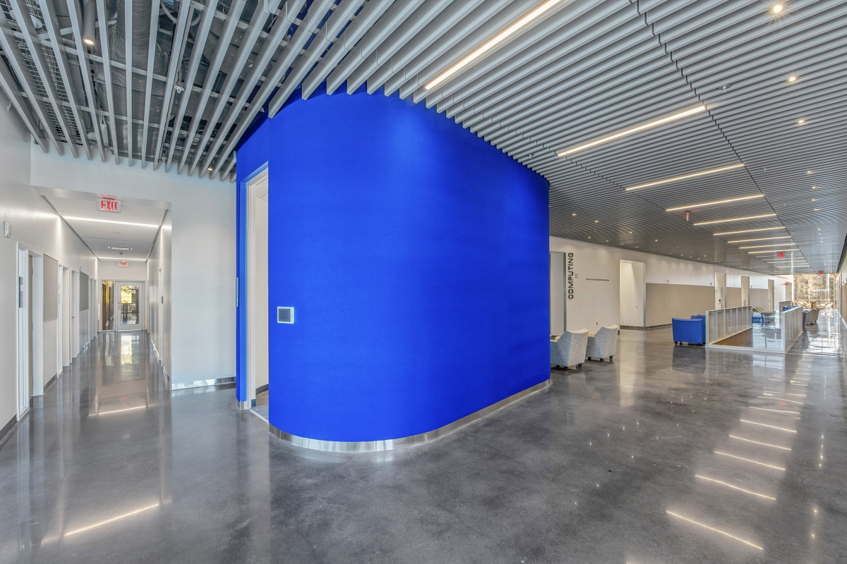 view down a neighborhood hallway with a blue pod conference room