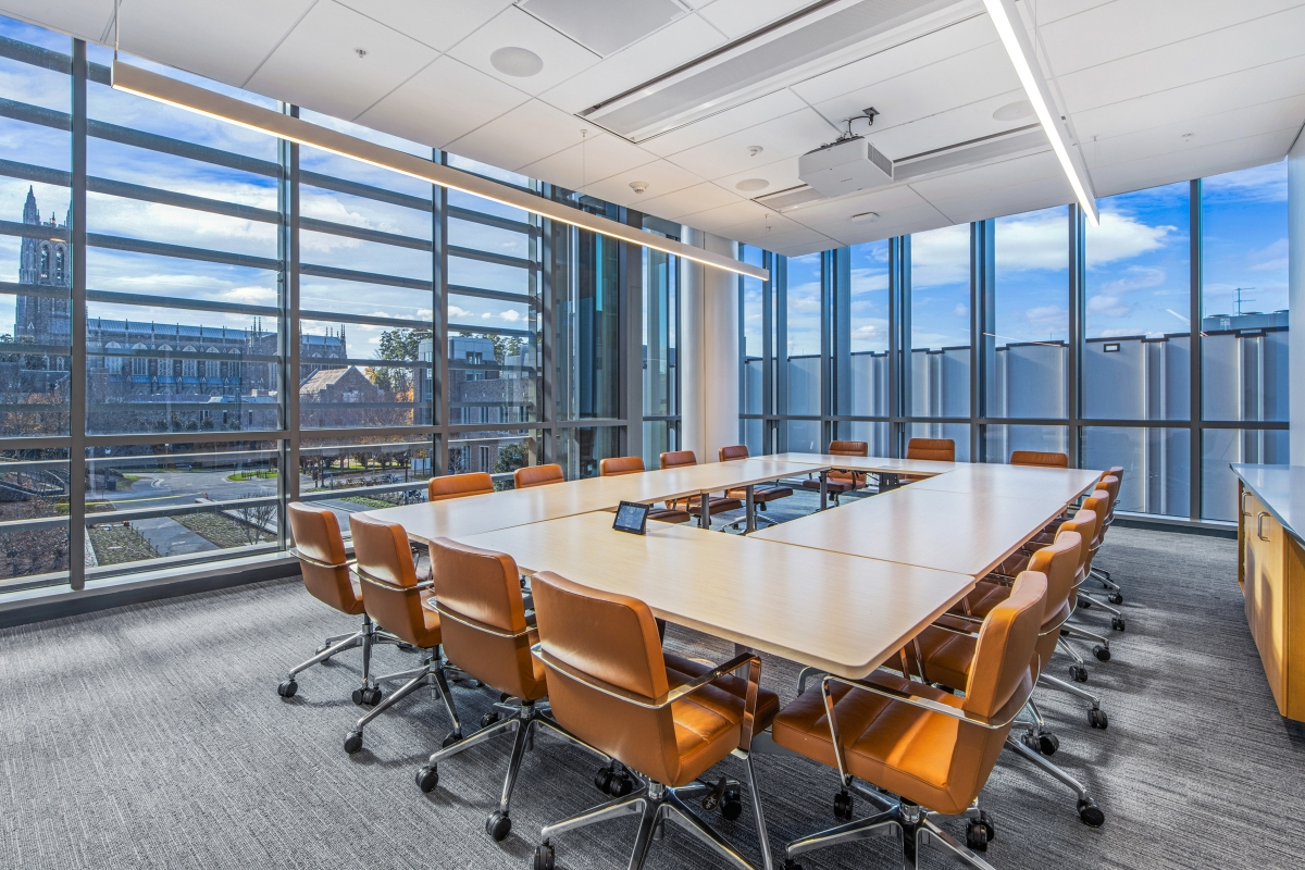 conference room with large table and chairs and a view of Duke Chapel in the background