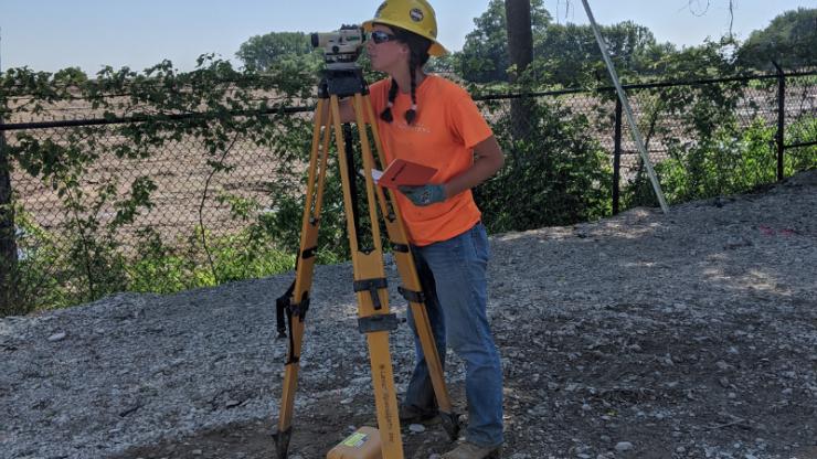 Caroline Heitmann using surveying equipment