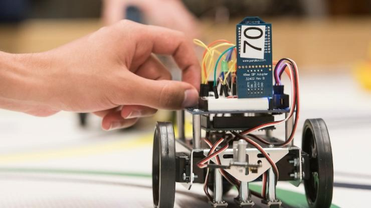 A student makes last-minute adjustments to his team's robot before final demonstrations