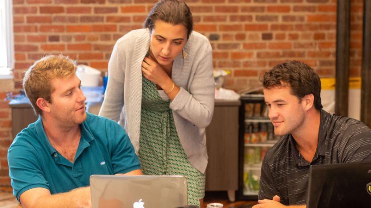 Three students huddle around an iMac