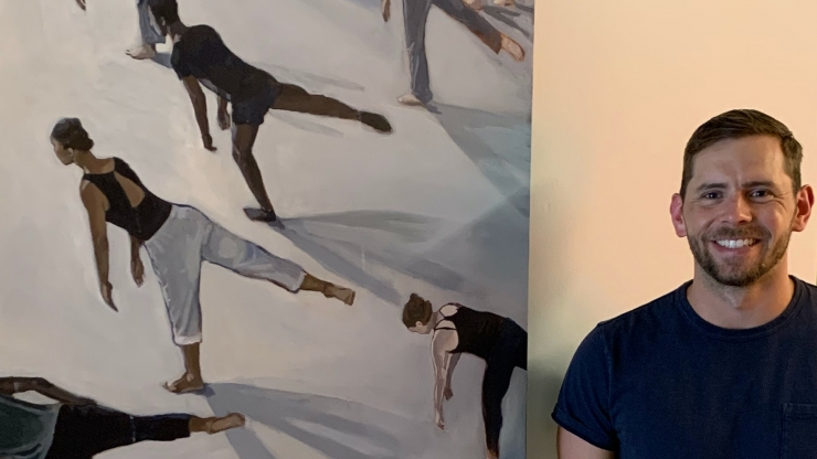 Clay Sanders next to painting of dancers