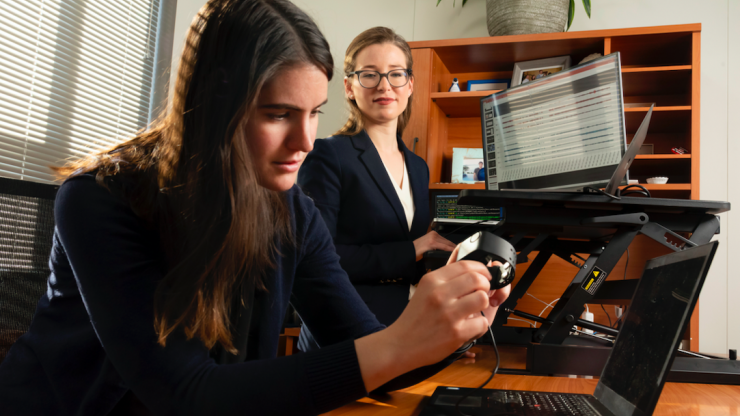 Ph.D. student Brinnae Bent prepares to download information from a wearable health monitoring device while assistant professor Jessilyn Dunn looks on. (Les Todd)