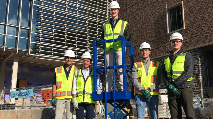 The scissor-lift safety device design team with their prototype across the street from where Skanska is construction Duke's newest engineering building.