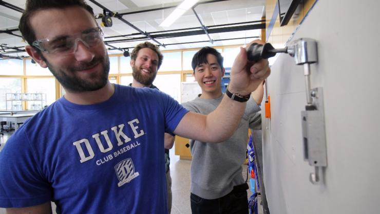 Duke students show off their adjustable wall hook for art galleries.