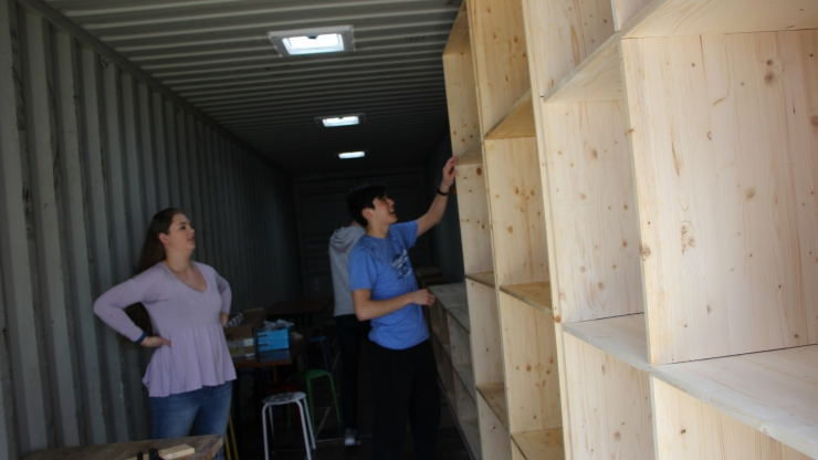 Students in the spring semester of Design 101 move shelves into a storage container, which will become a functioning design space. The team was recognized at the Global Innovation Challenge for their project.