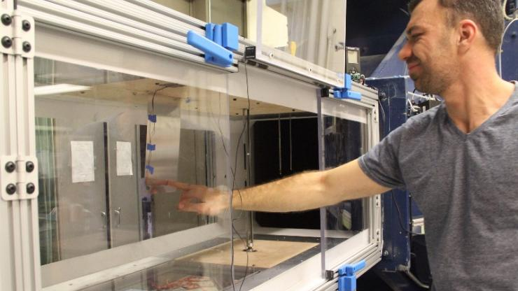 Dani Levin adjusts piezoelectric device in Duke's wind tunnel