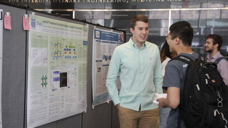 Clayton Connor answers questions at the Duke REU poster session held in Fitzpatrick Hall