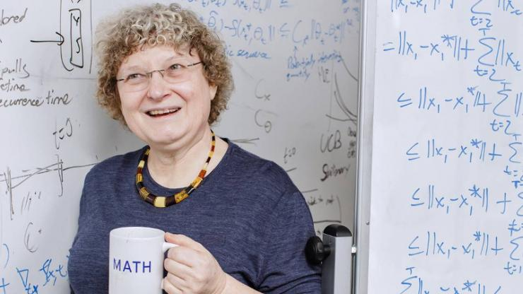 Ingrid Daubechies with math mug in front of white board with equations