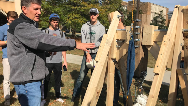 David Schaad demonstrates how to use a trebuchet to his engineering class