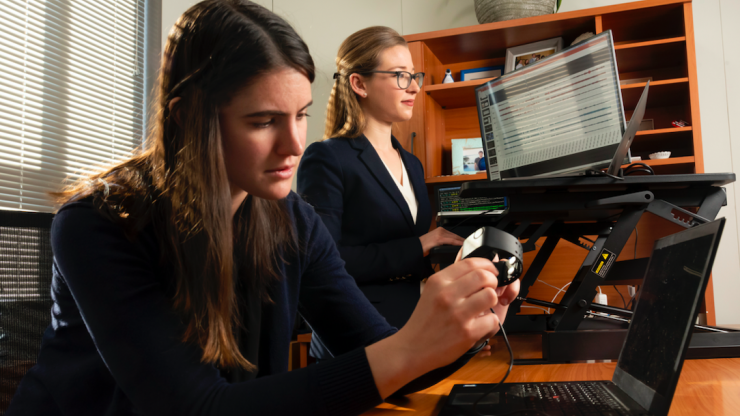 Jessilyn Dunn with PhD student Brinnae Bent, who is preparing to download information from a wearable health monitoring device