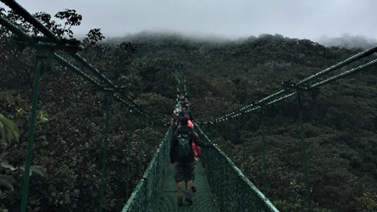 Students cross a wooden suspension bridge in the jungle with low overhanging clouds